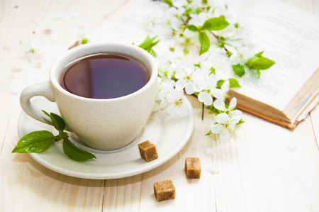 Foto de A cup of tea with spring flower cherry blossom and old book on a wooden background - Imagen libre de derechos