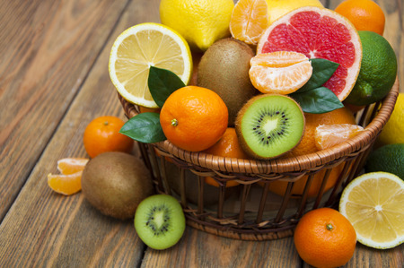 Foto de Fresh juicy citrus fruits in a basket on a wooden background - Imagen libre de derechos