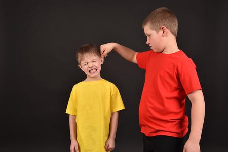 Foto de Bad behavior. Children. Two boys on a black background. - Imagen libre de derechos