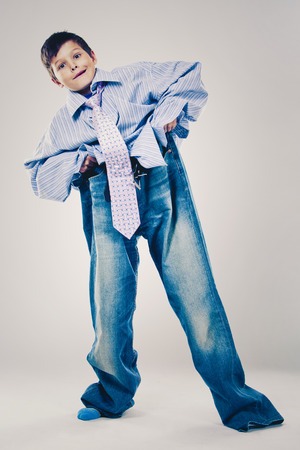 Photo pour Caucasian boy wearing his Dad's shirt, jeans and tie on light background. He is wearing big adult size clothes which are too big for him. - image libre de droit