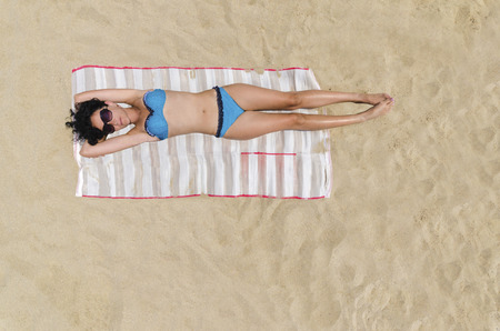 Bermuda Sunbathing, Beautiful brunette girl is sunbathing on an empty beach, aerial view from top
