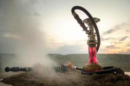 Foto de Hookah, traditional arabic waterpipe, direct sunset light, outdoor photo. Mountain background - Imagen libre de derechos