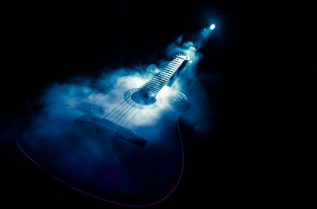 Photo pour Music concept. Acoustic guitar isolated on a dark background under beam of light with smoke with copy space. Guitar Strings, close up. Selective focus. Fire effects. Surreal guitar - image libre de droit