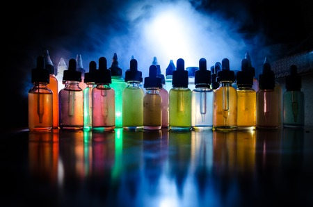 Photo for Vape concept. Smoke clouds and vape liquid bottles on dark background. Light effects. Useful as background or vape advertisement or vape background. - Royalty Free Image