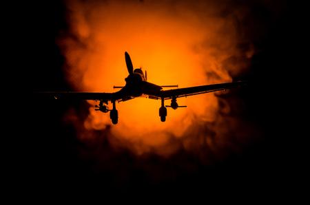 Foto de World war ii fighter plane at sunset or dark orange fire explosion sky. War scene. German figher at sky. Selective focus - Imagen libre de derechos