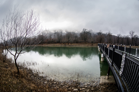 Photo pour Amazing landscape of bridge reflect on surface water of lake, fog evaporate from pond make romantic scene or Beautiful bridge on lake with trees at fog. Iron bridge over lake in misty morning. - image libre de droit