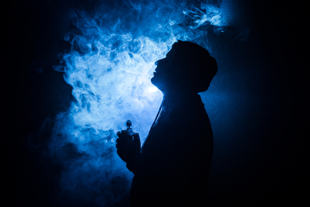 Photo for Vaping man holding a mod. A cloud of vapor. dark foggy toned background of clouds of smoke. Vaping an electronic cigarette with a lot of smoke. Vape concept. Selective focus - Royalty Free Image