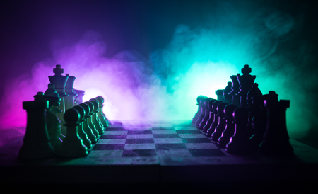 Foto de Chess board game concept of business ideas and competition and strategy ideas concep. Chess figures on a dark background with smoke and fog. Business leadership and confidence concept. Selective focus - Imagen libre de derechos