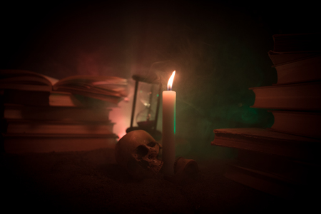 Foto de Wizard's Desk. A desk lit by candle light. A human skull, old books on sand surface. Halloween still-life background with a different elements on dark toned foggy background. Selective focus - Imagen libre de derechos