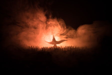 Photo for Lamp of wishes. Silhouette of a large crowd of people standing against a big lamp of wishes with toned light beams on foggy background. Dark night table decoration. Selective focus - Royalty Free Image