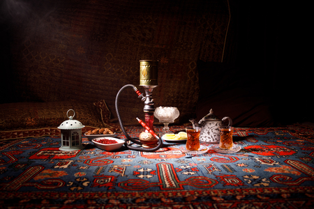 Photo for Hookah hot coals on shisha bowl making clouds of steam at Arabian interior. Oriental ornament on the carpet eastern tea ceremony. Stylish oriental shisha in dark with backlight. Selective focus - Royalty Free Image