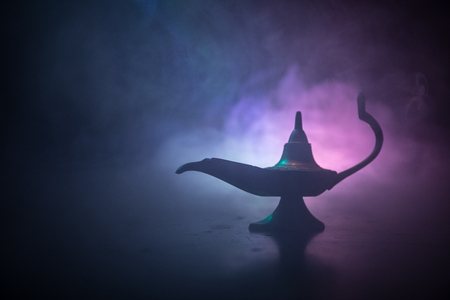 Photo for Antique Aladdin arabian nights genie style oil lamp with soft light white smoke, Dark background. Lamp of wishes concept. Selective focus - Royalty Free Image