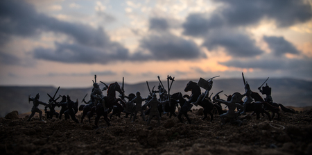 Foto de Medieval battle scene with cavalry and infantry. Silhouettes of figures as separate objects, fight between warriors on sunset foggy background. Selective focus - Imagen libre de derechos