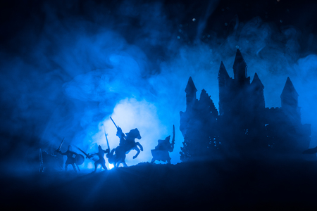 Photo pour Medieval battle scene with cavalry and infantry. Silhouettes of figures as separate objects, fight between warriors on dark toned foggy background with medieval castle. Selective focus - image libre de droit