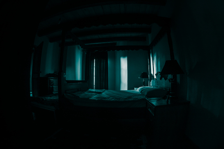 Foto de A creepy bedroom scenery, Antique scary bedroom with window . Dark room. Horror concept - Imagen libre de derechos