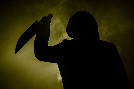 Foto de A dangerous hooded man standing in the dark and holding a knife. Face can not be seen. Committing a crime concept - Imagen libre de derechos
