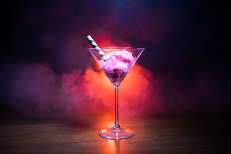 Photo for Martini glass filled with colorful fruit ice cream on dark background with toned light and fog. Selective focus - Royalty Free Image