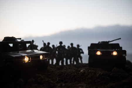 Foto de Military patrol car on sunset background. Army war concept. Silhouette of armored vehicle with soldiers ready to attack. Artwork decoration. Selective focus - Imagen libre de derechos