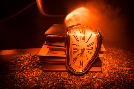 Photo for Time Concept. Distorted soft melting clock on the old books. With dark toned foggy background. Selective focus - Royalty Free Image