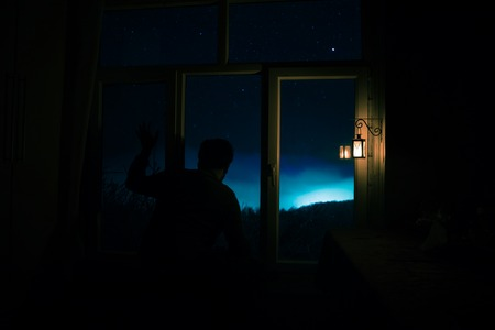 Photo for Silhouette of a man looking a dreamlike galaxy through a window. Fantasy picture with old vintage lantern at the window inside dark room. - Royalty Free Image
