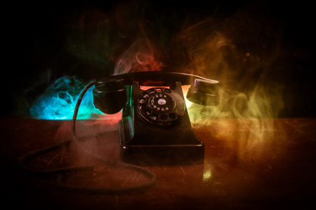 Photo pour old black telephone on old wood plank with art dark background with fog and toned light. empty space. Selective focus - image libre de droit
