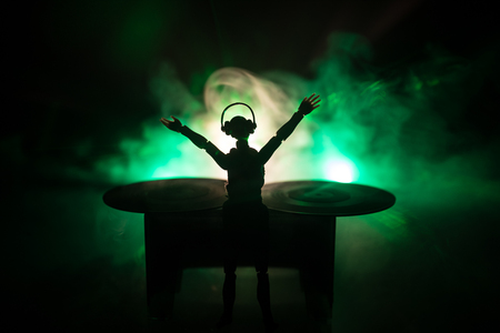 Photo for Dj club concept. Woman DJ mixing, and Scratching in a Night Club. Girl silhouette on dj's deck, strobe lights and fog on background. Creative artwork decoration with toy. Selective focus - Royalty Free Image