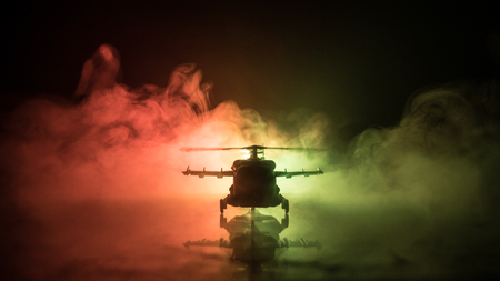 Foto de Silhouette of military helicopter ready to fly from conflict zone. Decorated night footage with helicopter starting in desert with foggy toned backlit. Selective focus. War concept - Imagen libre de derechos
