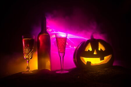 Foto de Halloween wine party theme. Two glasses of wine and bottle with Halloween - old jack-o-lantern on dark toned foggy background. Scary Halloween pumpkin - Imagen libre de derechos