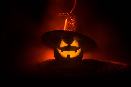 Photo pour Halloween concept. Jack-o-lantern smile and scary eyes for party night. Close up view of scary pumpkin with witch hat on at dark foggy background. Selective focus. Empty space - image libre de droit