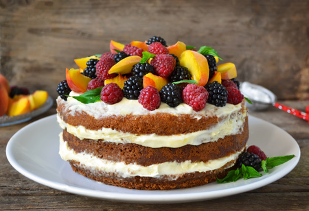 Photo pour Naked cake with cream, decorated with raspberries, blackberries, peaches - image libre de droit