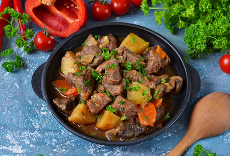 Photo for Meat goulash with vegetables, potatoes and mushrooms on concrete, grunge background - Royalty Free Image