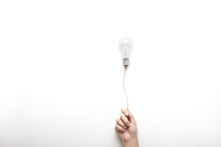 Photo pour Hand holding  light bulb on rope floating on white background with texting space, idea concept. - image libre de droit
