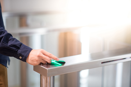 Photo pour Male hand using smart card to open automatic gate machine in office building - image libre de droit