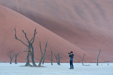 Photo for Young male photographer and traveler taking photo of dead tree in deadvlei (Sossusvlei), famous natural landmark in Namib desert of Namibia, Africa. Travel photography concept - Royalty Free Image