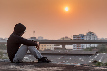 Photo pour Young Asian man sitting on rooftop of abandoned building with depression stress out during sunset time in the city. Major depressive disorder concept - image libre de droit