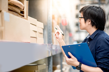 Foto de Young Asian man doing stocktaking of product in cardboard box on shelves in warehouse by using clipboard and pen. physical inventory count concept - Imagen libre de derechos