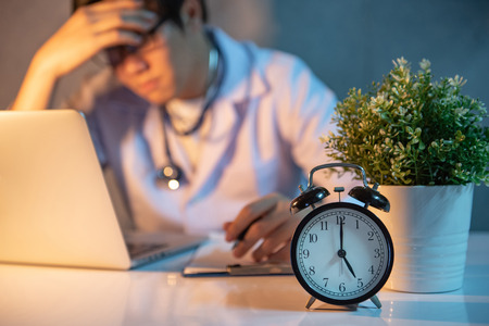 Photo for Overworked doctor working with laptop computer in hospital clinic. Male practitioner feeling stressed and tried during hard working time in medical center. Focus on table clock. - Royalty Free Image