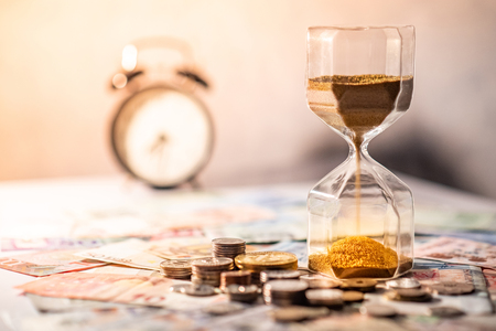 Foto de Sand running through the shape of hourglass on table with banknotes and coins of international currency. Time investment and retirement saving. Urgency countdown timer for business deadline concept - Imagen libre de derechos