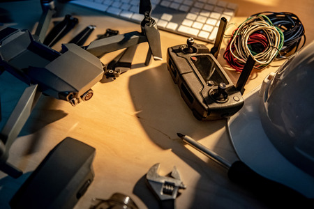 Photo pour Drone maintenance with spare parts on the table. propeller battery, remote control, screwdriver and cables. Self inventive repairing drone or unmanned aerial vehicle (UAV) photography concepts - image libre de droit