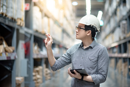 Foto de Young Asian man worker wearing safety helmet and eyeglasses doing stocktaking of product in cardboard box on shelves in warehouse by using digital tablet and pen. Physical inventory count concept - Imagen libre de derechos