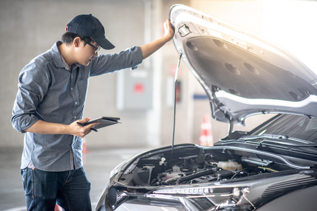 Foto de Asian auto mechanic holding digital tablet checking car engine under the hood in auto service garage. - Imagen libre de derechos