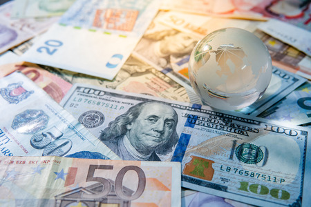 Photo pour Global business and economy. World globe crystal glass on various international money banknotes. Currency exchange rate. Financial investment concept - image libre de droit