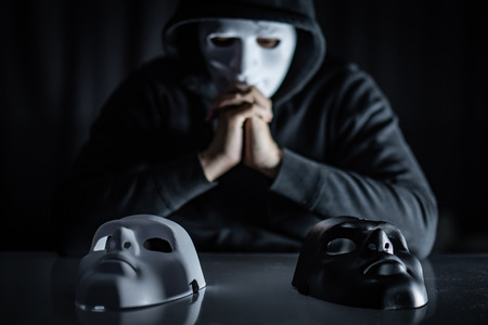 Foto de Hoodie man wearing mystery mask choosing black or white mask on the table. Anonymous social masking. Major depressive disorder or bipolar disorder. Halloween concept - Imagen libre de derechos