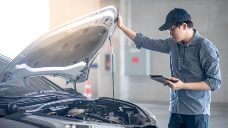 Foto de Asian auto mechanic holding digital tablet checking car engine under the hood in auto service garage. Mechanical maintenance engineer working in automotive industry. Automobile servicing and repair - Imagen libre de derechos