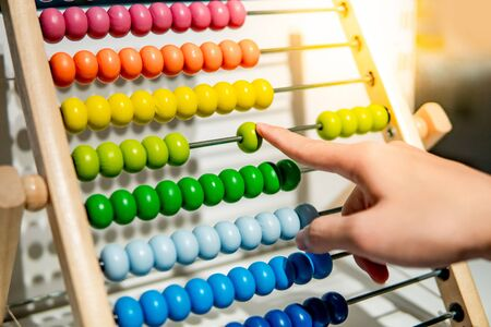 Foto de Male hand calculating with beads on wooden rainbow abacus for number calculation. Mathematics learning concept - Imagen libre de derechos