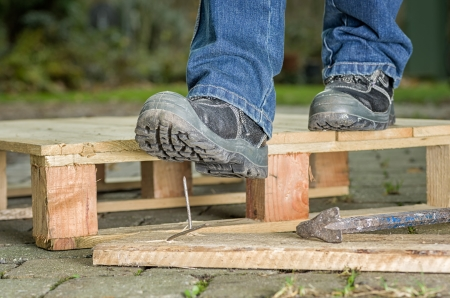 Photo pour Worker with safety boots steps on a nail - image libre de droit