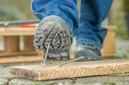 Foto de Worker with safety boots steps on a nail - Imagen libre de derechos
