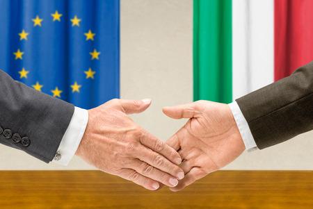 Representatives of the EU and Italy shake hands