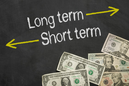 Photo pour Text on blackboard with money - Long term and short term - image libre de droit