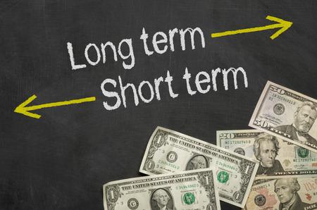 Foto de Text on blackboard with money - Long term and short term - Imagen libre de derechos